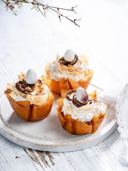 Coupes de pâte fantaisie phyllo avec meringue et chocolat fondu.