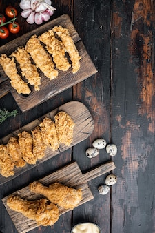 Coupes de poulet frit croustillantes au kentucky sur fond de bois foncé, vue de dessus, avec un espace pour le texte.
