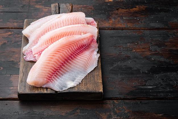 Coupes de viande de filet de poisson tilapia, sur bois foncé