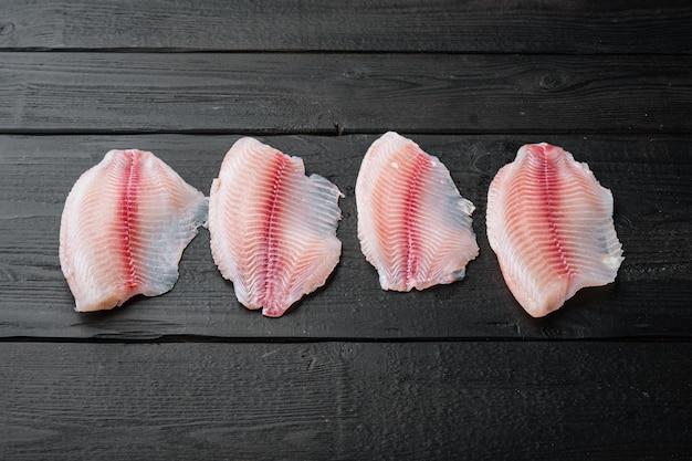 Coupes de viande de filet de poisson tilapia, sur table en bois noir, vue du dessus