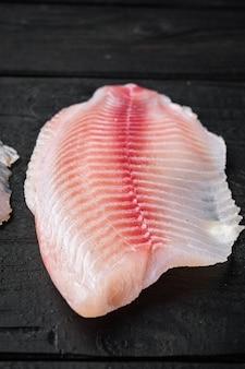 Coupes de viande de filet de poisson tilapia, sur table en bois noir