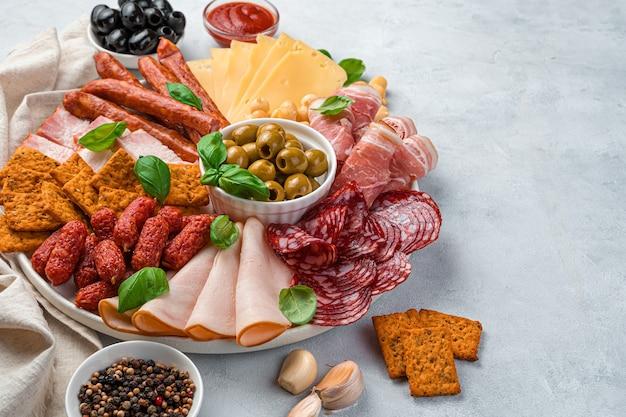 Coupes de viande et saucisses de différents types, fromages et plus encore sur une planche sur fond gris.