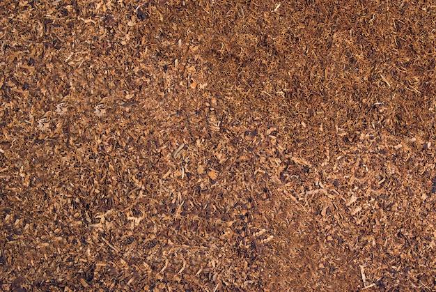 Des coupes en vrac de tabac séché forment une texture de fond doré