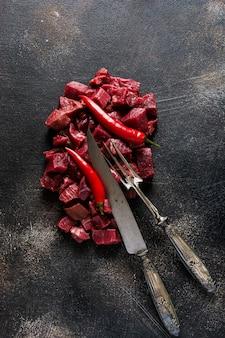 Coupez le bœuf en petits morceaux avec du sel de mer, des herbes séchées et des piments sur fond d'ardoise foncée ou de béton. vue de dessus.