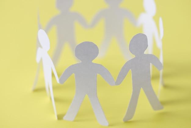 Coupez les gens de papier formant le cercle d'union sur le fond jaune