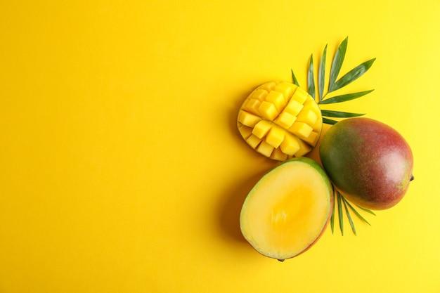 Coupez les mangues mûres et l'espace pour le texte sur fond de couleur, vue de dessus