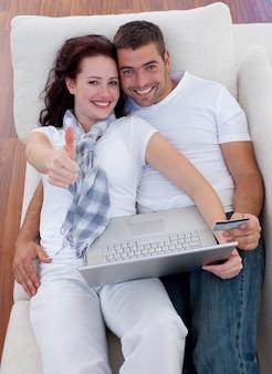 Couple achetant en ligne à la maison avec thums