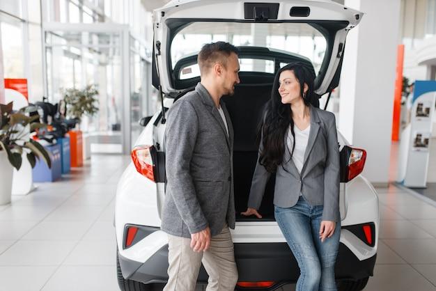 Couple achetant une nouvelle voiture dans la salle d'exposition, homme et femme près du coffre ouvert.