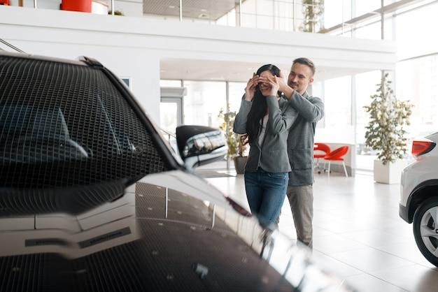 Couple achetant une nouvelle voiture dans la salle d'exposition, surprise pour femme.