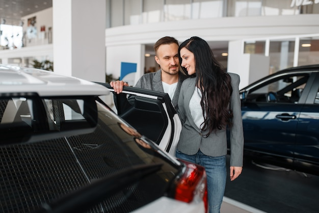Couple achetant une nouvelle voiture dans la salle d'exposition