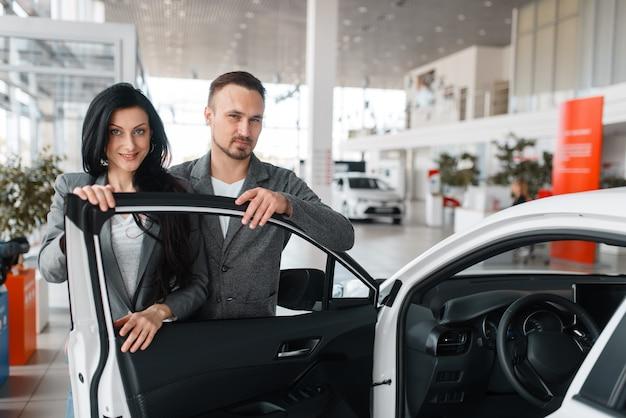 Couple achetant une nouvelle voiture dans la salle d'exposition.