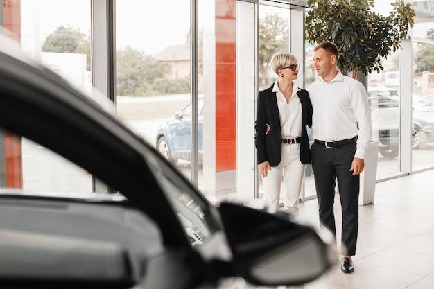 Couple achetant la voiture. paire dans un salon de l'automobile.