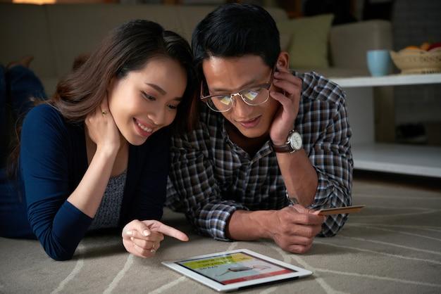 Couple achète des choses en ligne en utilisant l'onglet numérique