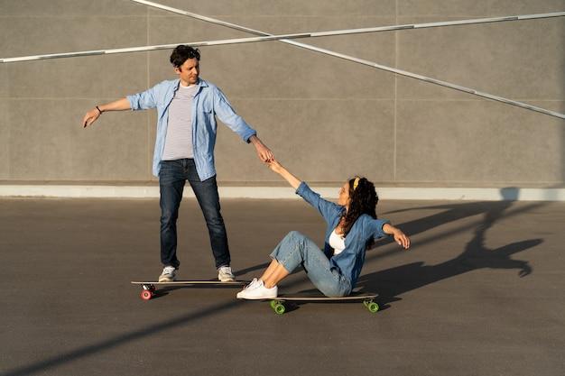 Un couple actif aime faire du longboard ensemble dans la rue de la ville d'été, un homme enseigne le skateboard à une femme