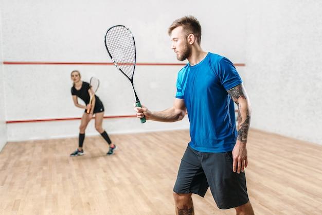 Un couple actif avec des raquettes joue au squash dans un club d'entraînement en salle.