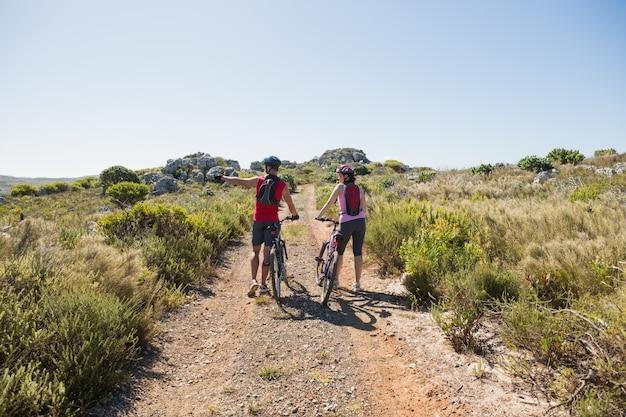 Couple actif à vélo dans la campagne à la recherche sur le côté