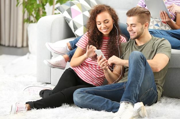 Couple d'adolescents écoutant de la musique avec un téléphone mobile dans le salon