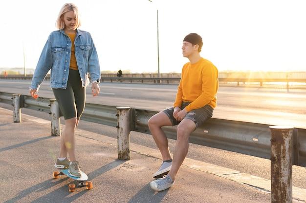 Couple d'adolescents élégant avec un longboard sur le pont pendant le coucher du soleil