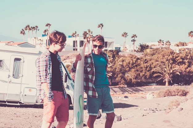 Couple d'adolescents regardant le même téléphone et parlant ensemble sur une table de surf à l'intérieur, prêts à aller surfer à la plage
