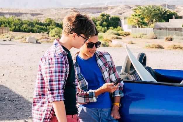 Couple d'adolescents souriant et s'amusant ensemble à la plage, surfeur et surf - surf - 20 ans avec lunettes et lunettes de soleil en plein air attendre d'aller surfer