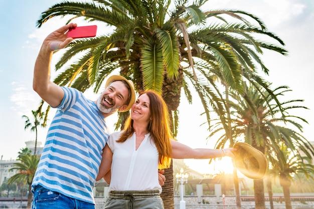 Couple adulte datant prenant un selfie à barcelone au coucher du soleil