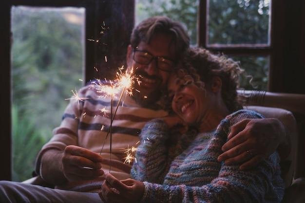 Un couple adulte heureux célèbre avec amour à la maison pendant les vacances d'hiver