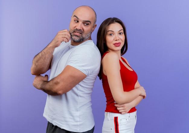 Couple adulte impressionné debout dos à dos homme regardant femme toucher le menton et elle gardant les mains croisées à la recherche