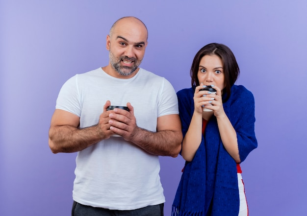Couple adulte impressionné femme enveloppée dans un châle homme souriant à la fois tenant une tasse en plastique de café à la recherche