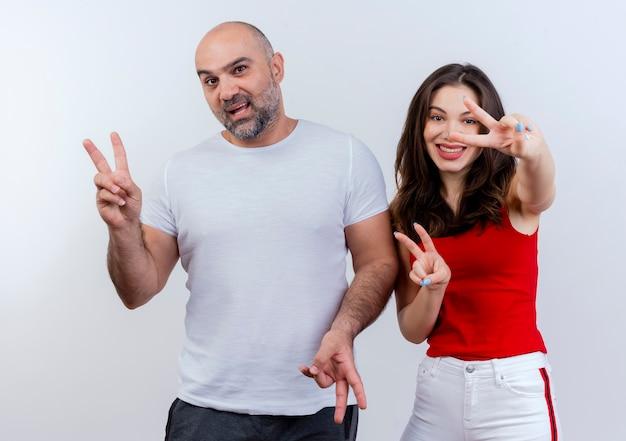 Couple adulte a impressionné l'homme et la femme souriante faisant des signes de paix et à la recherche