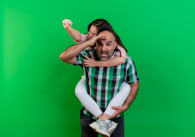 Couple adulte a impressionné l'homme regardant à distance tenant une femme joyeuse sur son dos femme serrant le poing