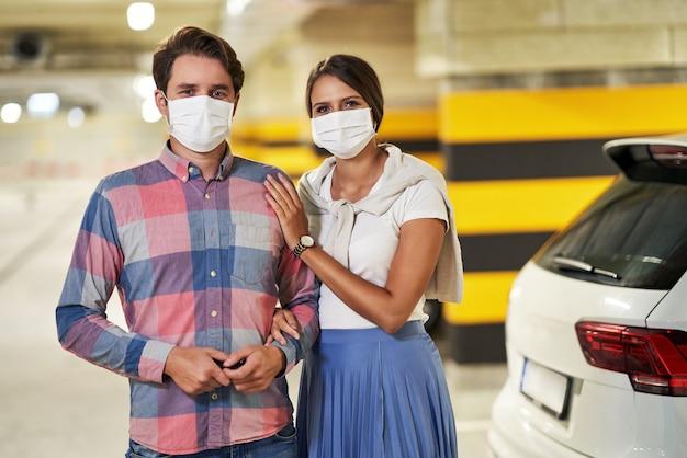 Couple adulte portant des masques dans un parking souterrain