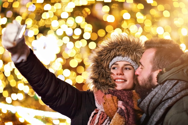 Couple adulte prenant selfie dans la ville pendant la période de noël