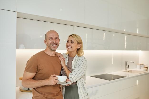 Couple d'adultes aimant souriant tout en se tenant dans l'intérieur de la cuisine blanche à la maison
