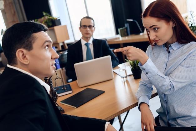 Un couple d'adultes demande le divorce dans un cabinet d'avocats.