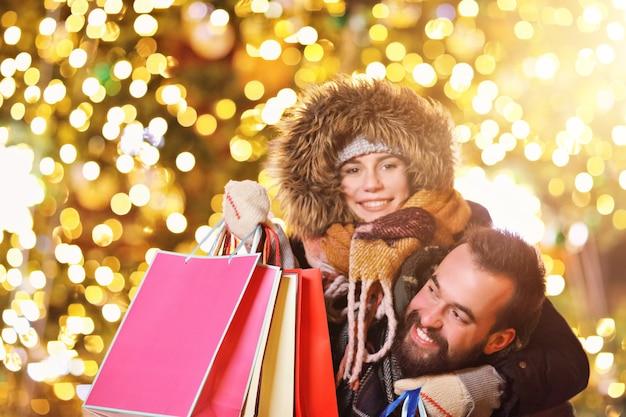 Couple d'adultes faisant du shopping dans la ville pendant la période de noël