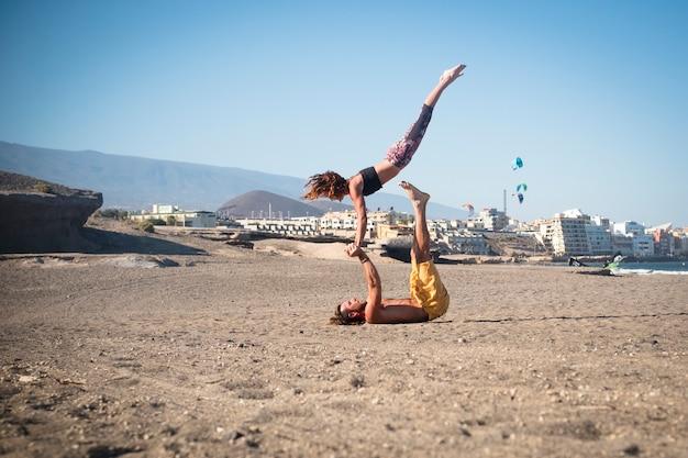 Couple d'adultes faisant du yoga ou de l'acroyoga en silence à la plage - femme et homme concentrés pour travailler ensemble - ville en arrière-plan