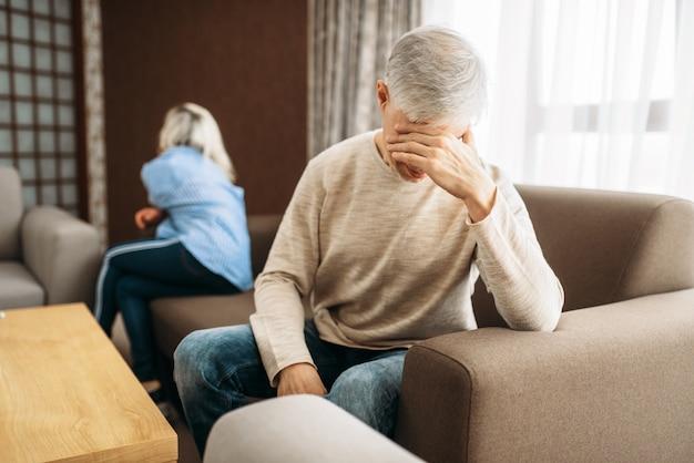 Couple d'adultes à la maison, querelle de famille ou conflit. mari et femme d'âge mûr assis sur un canapé avec le dos l'un à l'autre, problèmes de relation