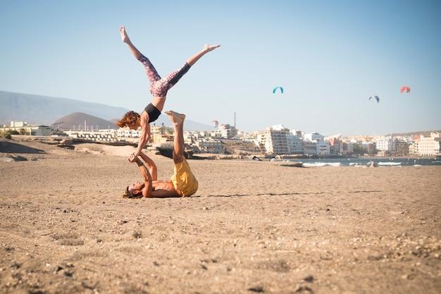 Couple d'adultes en relation ou en amitié faisant du sport comme l'acroyoga ou le yoga ensemble à la plage sur le sable - seuls et isolés avec la ville en arrière-plan