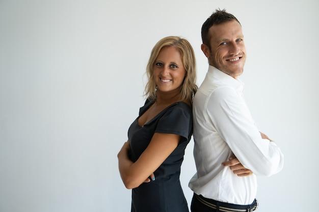 Couple d'affaires confiant joyeux debout dos à dos et en regardant la caméra