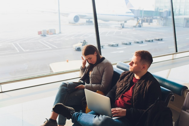 Couple d'affaires élégant travaillant avec ordinateur portable et téléphone assis dans la salle d'attente de l'aéroport. concept de voyage d'affaires.