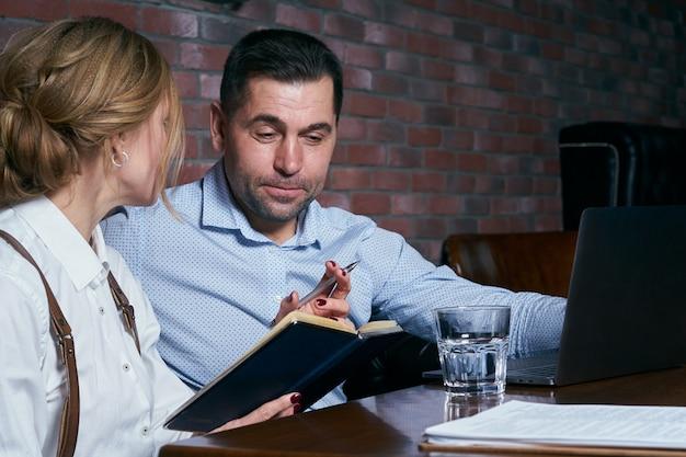 Couple d'affaires heureux travaillant ensemble sur ordinateur portable dans un restaurant