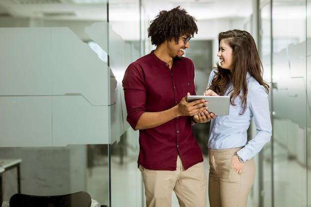 Couple d'affaires multiethnique à l'aide d'une tablette numérique au bureau