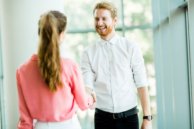 Couple d'affaires se serrant la main au bureau