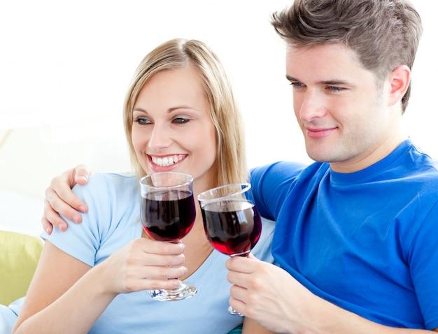 Couple affectueux, boire du vin assis sur un canapé