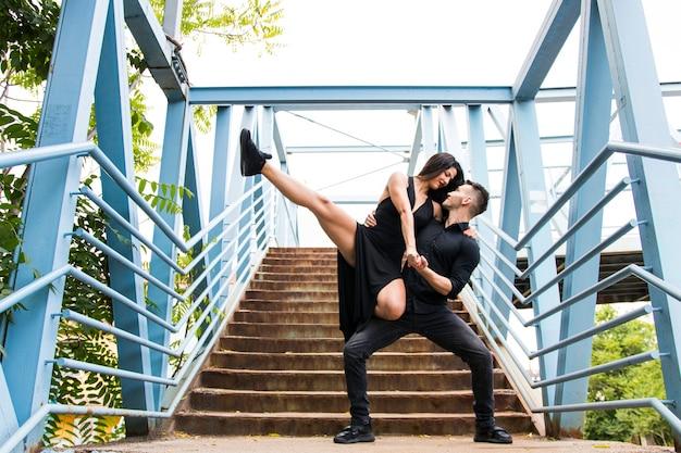 Couple affectueux dansant sur le pont