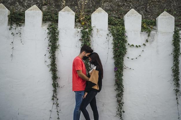 Couple affectueux debout près d'un mur décoré