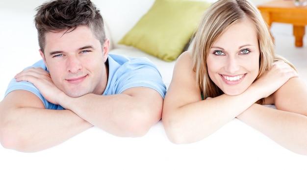 Couple affectueux regardant la caméra sur un canapé