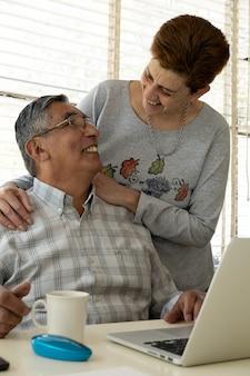 Couple affectueux souriant à l'aide d'un ordinateur portable