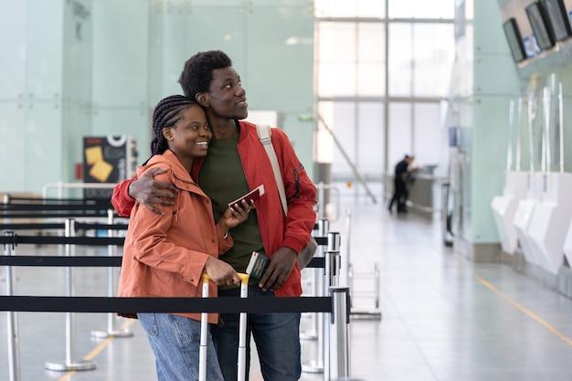 Un couple africain libre de voyager attend l'enregistrement pour le vol à l'aéroport