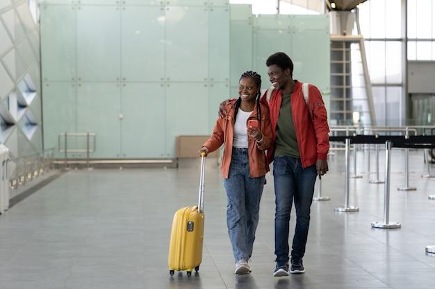 Un couple africain marche avec des bagages dans un aéroport vide portant ses bagages